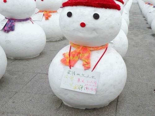 大家是不是都很好奇,为什么这些雪人长的都完全一样啊,是怎么做出来的?原来这些雪人也是模式化产品,所以才能如此整齐划一。工人有两个大小不同的圆形模具,把雪撮进模具里用木棍捣实,刮平,然后分别打开模具,将大一点的的雪球放在底下,小的放在上边。雪人的雏形就做好了,再按上黑眼睛,装上鼻子,戴上帽帽,扎上围巾,一个雪人就做好了,大家看出来了吗?