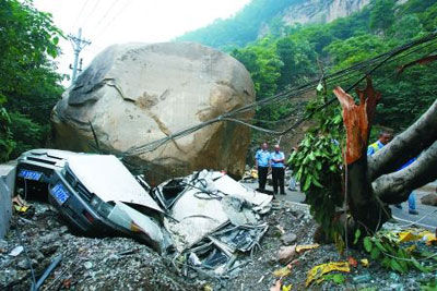 昨日,江北区郭家沱望江铜锣村,山上滚落的巨石将路边停靠的小车压扁。 记者 邹飞 实习生 周怡 摄