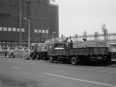 两辆货车并排停在松浦大桥下的绿地旁,工人们正在从车上向下卸货。