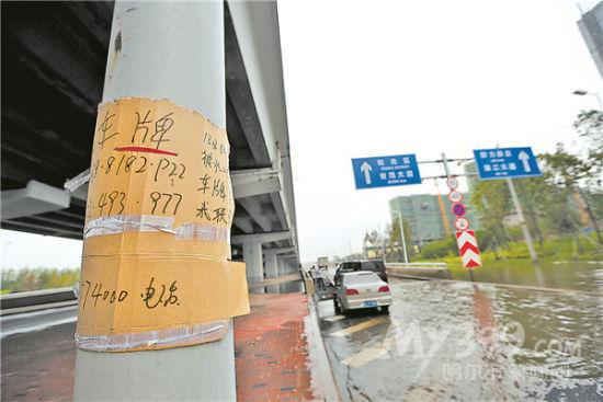 寻车牌因车牌被水冲掉,一些车主将牌照号贴在路杆上,希望能找回.