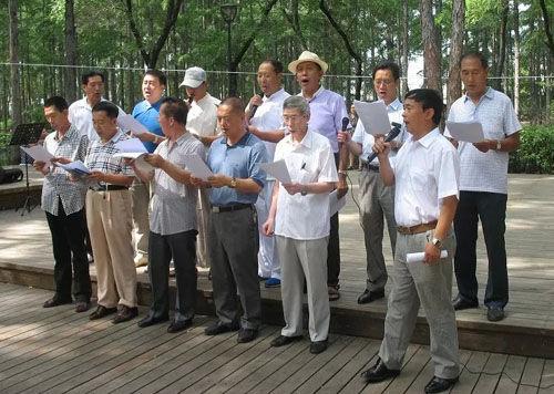 8月4日,市人民公园绿树林中的休闲坪上成了市老年大学艺术团团员们